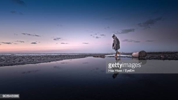 Woman Walking Against Sea During Sunset