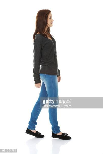 woman walking against white background - van de zijkant stockfoto's en -beelden