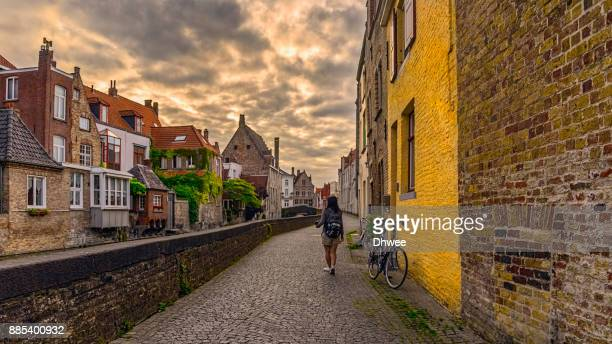 woman walking alone in bruges against sunrise - bruges stock pictures, royalty-free photos & images