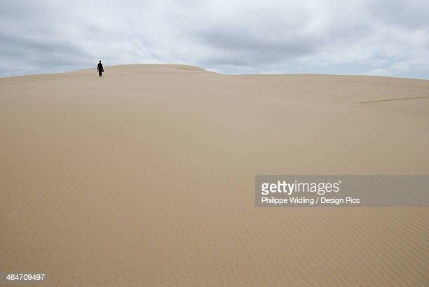 A Woman Walking Alone On A Sand Dune In The Distance