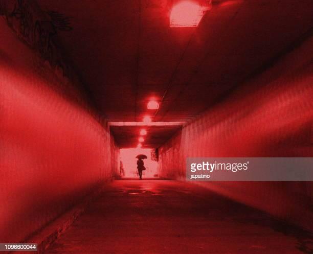 a woman walking alone through a dark tunnel - verbrechensopfer stock-fotos und bilder