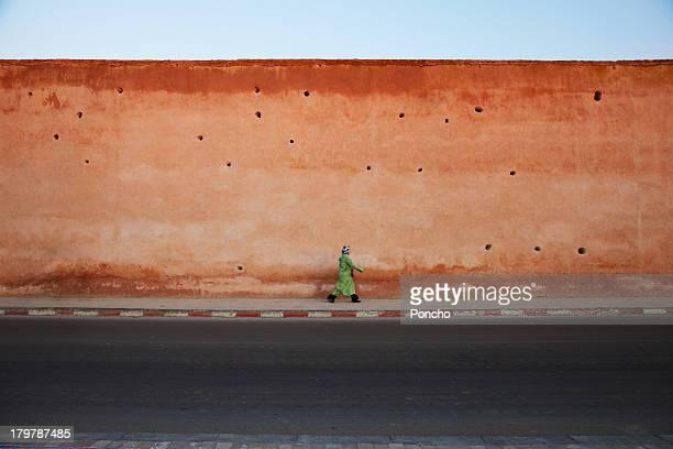 woman walking along a clay wall