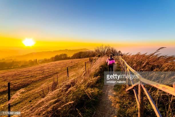 woman walking along a footpath at sunset, italy - marche italia foto e immagini stock