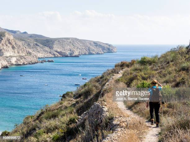 Woman walking along a path of for a dirt track of mountain of excursion, with a rucksack and a hat, a day of the sun and blue sky  on the sea.  Cabo de Gata - Nijar Natural Park, Biosphere Reserve, Almeria,  Andalusia, Spain