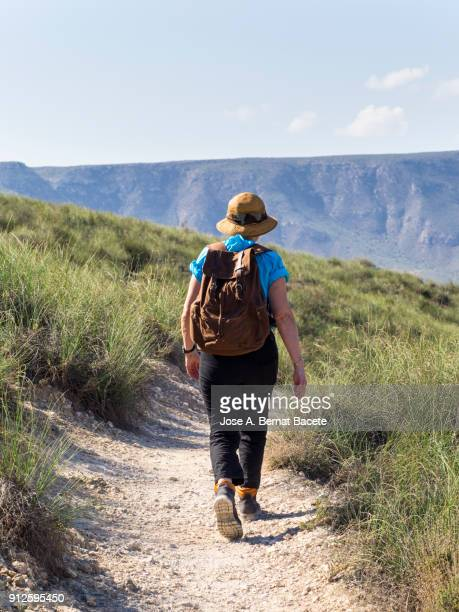 woman walking along a path of for a dirt track of mountain of excursion, with a rucksack and a hat, a day of the sun and blue sky.  cabo de gata - nijar natural park,  almeria,  andalusia, spain - hot spanish women stock pictures, royalty-free photos & images