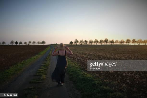 woman walking along a rural road, deux-sevres, nouvelle aquitaine, france - deux sevres fotografías e imágenes de stock