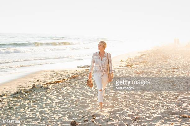 Woman walking along a sandy beach by the ocean.