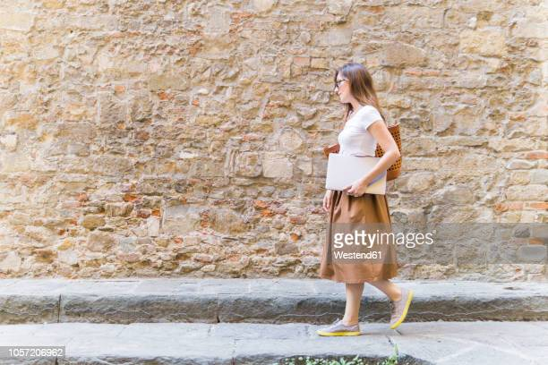 Woman walking along a stone wall carrying laptop