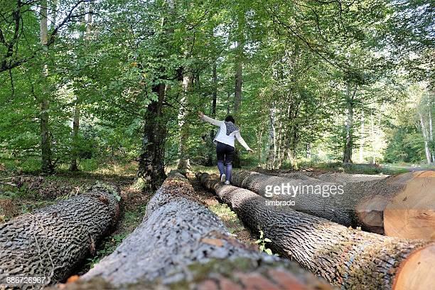 Woman walking along a tree trunk, Poitiers, France