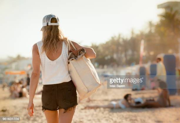 woman walking along beach, rear view, sitges, catalonia, spain - woman carrying tote bag stock photos and pictures