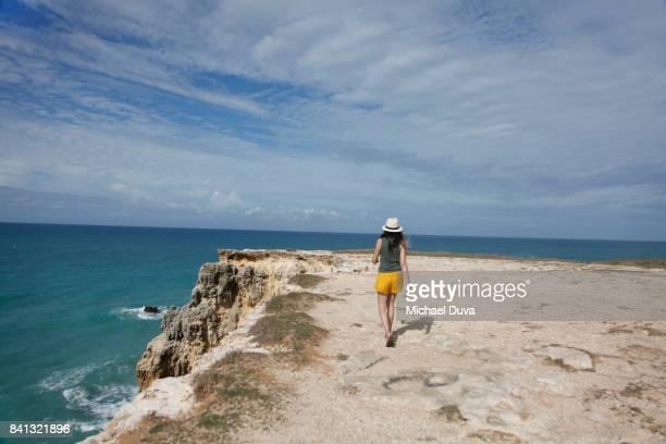 woman walking along cliff abutting ocean - paisajes de puerto rico fotografías e imágenes de stock