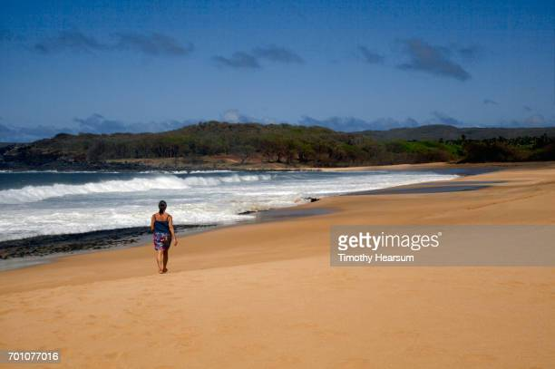 woman walking along deserted sandy beach - timothy hearsum stock pictures, royalty-free photos & images