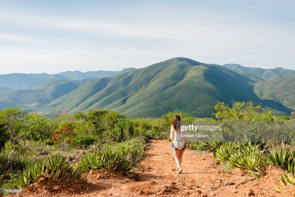 Woman walking along dirt pathway, rear view, Hierve el Agua, Oaxaca, Mexico. : Stock-Foto