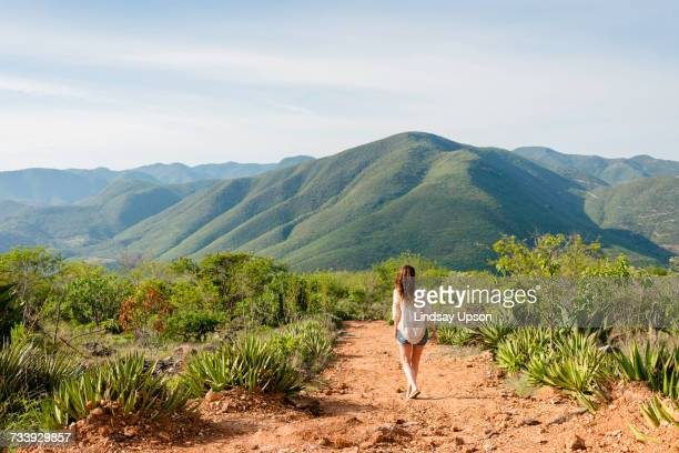 Woman walking along dirt pathway, rear view, Hierve el Agua, Oaxaca, Mexico.