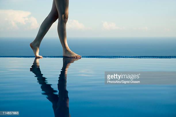 Woman walking along edge of infinity pool, low section