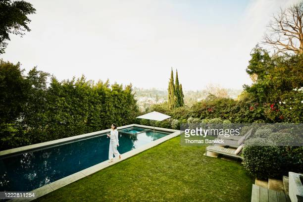 woman walking along edge of pool in backyard - paradise stock pictures, royalty-free photos & images