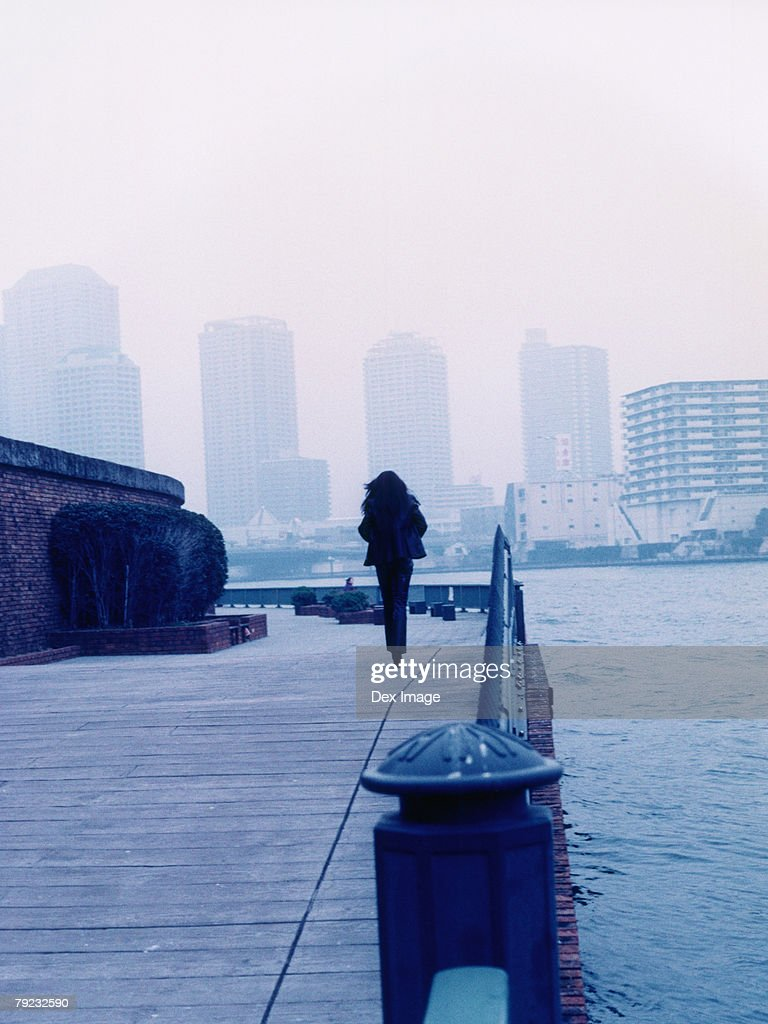 Woman walking along jetty, Tokyo city in background : Stock Photo