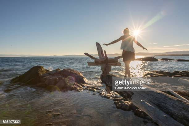 woman walking along log on beach to make driftwood sculpture - vancouver island stock pictures, royalty-free photos & images