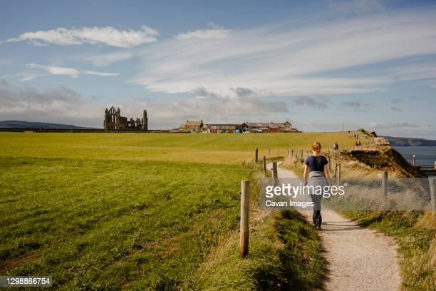 woman walking along path between whitby and robinshood bay with - ヨークシャー ストックフォトと画像