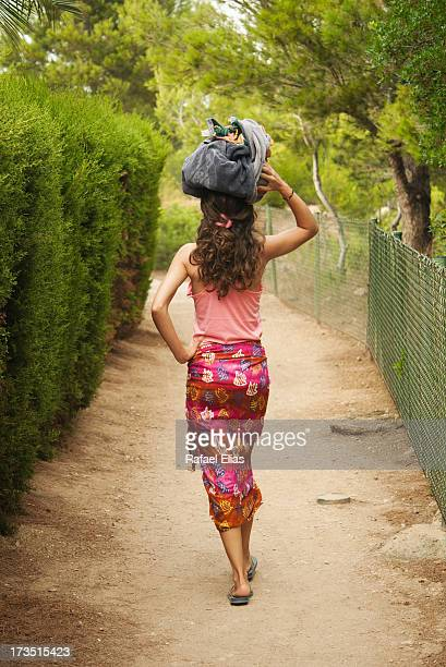 Woman walking along path with package on her head