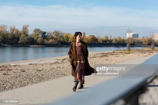 woman walking along rhine river, strandbad, mannheim, germany - ロングコート ストックフォトと画像