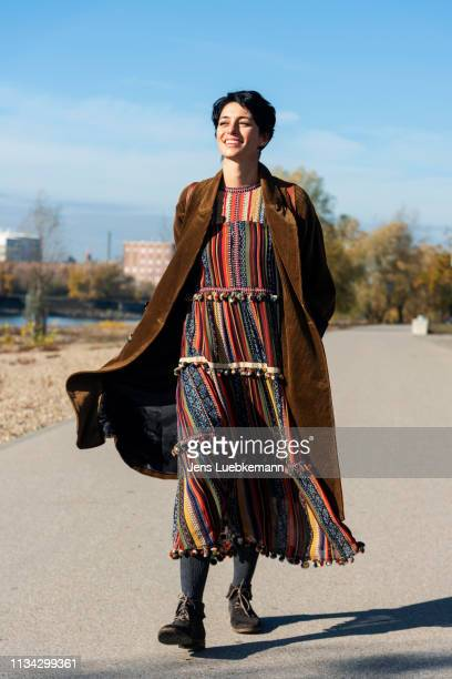 woman walking along rhine river, strandbad, mannheim, germany - long coat stock pictures, royalty-free photos & images