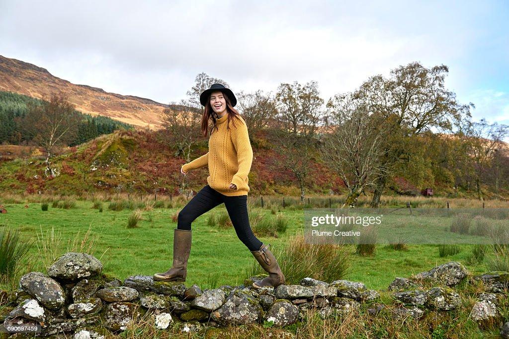 Woman walking along stone wall : Stock Photo