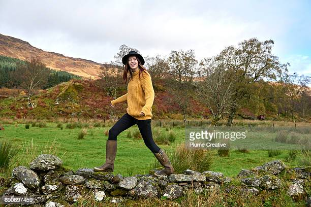 woman walking along stone wall - gummistiefel frau stock-fotos und bilder