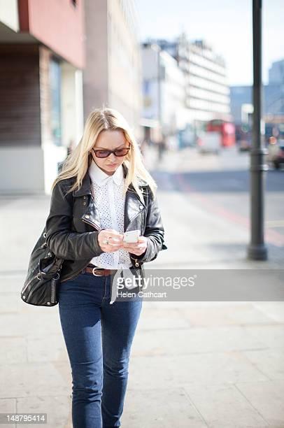 Woman walking along street looking at phone