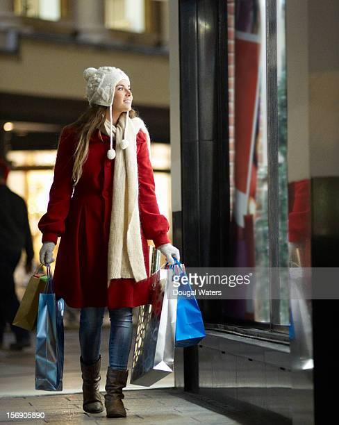 Woman walking along street looking in shop window.