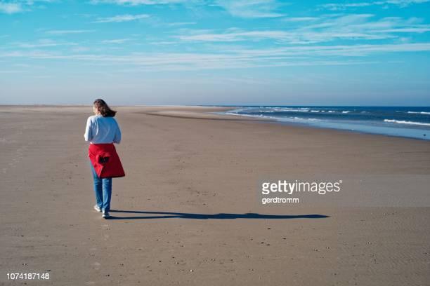 woman walking along the beach in autumn, juist, east frisia, lower saxony, germany - lower back - fotografias e filmes do acervo