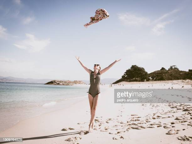 woman walking along the beach in the cies islands - spain stock pictures, royalty-free photos & images
