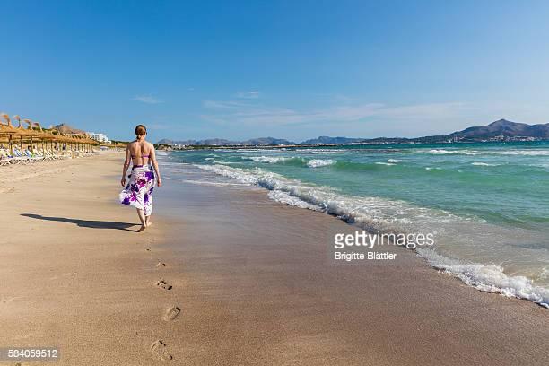 Woman walking along the beach of playa de Muro, Mallorca
