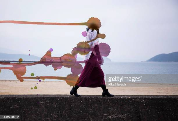 a woman walking along the beach which became a painting where the head turned red - ええじゃないか 発祥の地 ストックフォトと画像