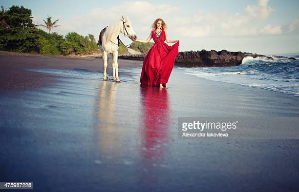 Woman walking along the beach with a horse