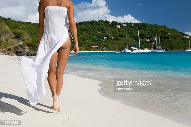 woman walking along the shore in virgin islands - sarong stock photos and pictures