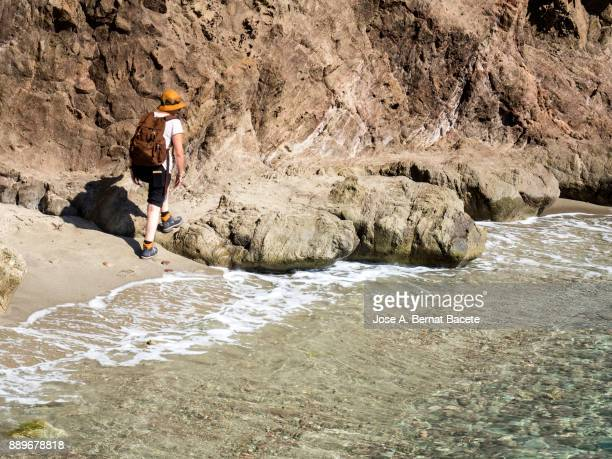 Woman walking along the shore of a beach of sand and rocks of excursion, with a rucksack and a hat. Sirens Reef, Cabo de Gata - Nijar Natural Park, Almeria,  Andalusia, Spain.