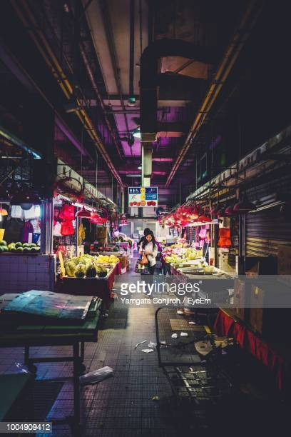 woman walking amidst illuminated market stall - one night stand stock-fotos und bilder