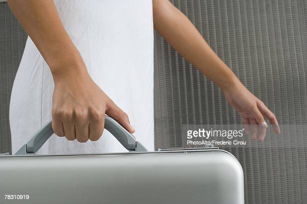 Woman walking and carrying briefcase, cropped view of hands