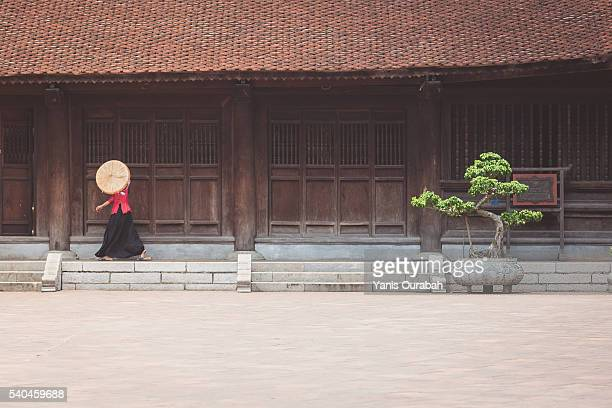 Woman walking and entering in a wooden temple in traditional clothes in Hanoi, Vietnam