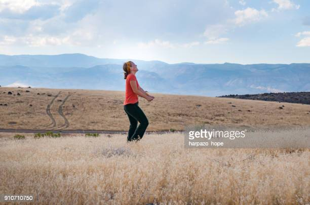 Woman walking and laughing in a field.