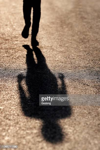 Woman walking and projecting long shadow on the street. Hanoi. Vietnam.