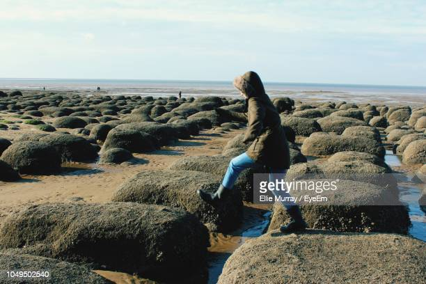 woman walking at beach against sky - lincolnshire stock pictures, royalty-free photos & images