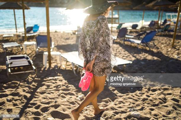 Woman Walking At Beach In Search Of Perfect Sunbed