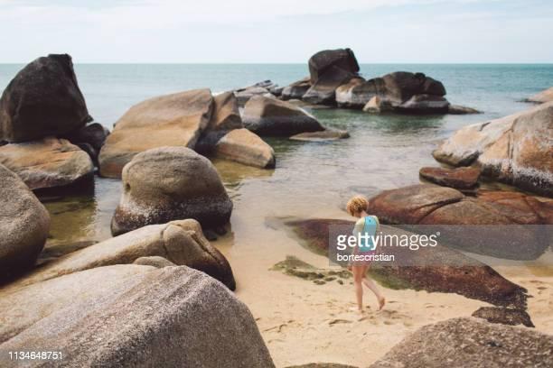 woman walking at beach - bortes stock-fotos und bilder