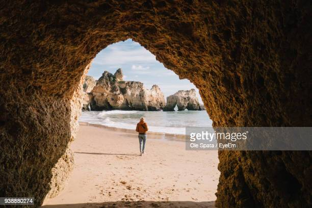 woman walking at beach seen through cave - lagos portugal stock pictures, royalty-free photos & images