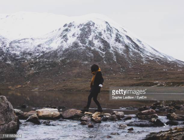 woman walking at lakeshore against snowcapped mountains - inverness scotland stock pictures, royalty-free photos & images