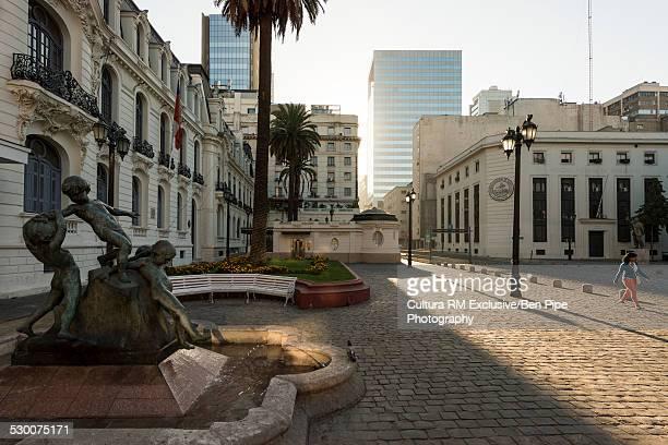 Woman walking at sunrise near Municipal Theatre, Santiago, Chile