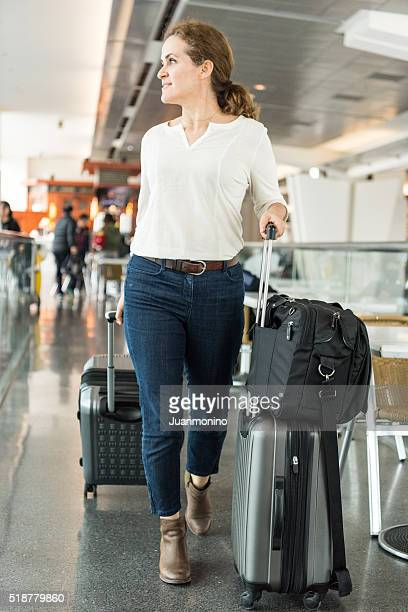 Woman walking at the airport walkway pulling rolled-on suitcases