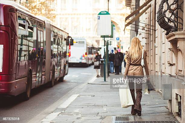 Woman walking at the bus stop with shopping bags